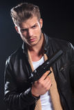 Hitman in leather clothes holding a big gun in his hand. Young hitman in leather clothes holding a big gun in his hand ondark background Stock Photo