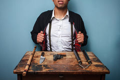Hitman showing off his weapons. Dangerous hitman with various weapons at old desk Stock Photography