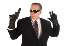 Hitman surrendering. Hitman wearing a suit and sunglasses holding his hands and gun up to the side in surrender Stock Photos