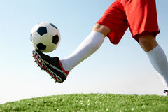 Hitting the ball. Horizontal image of soccer ball being kicked by footballer against blue sky Stock Photos