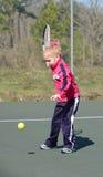 Hitting a tennis ball. Little girl hitting a tennis ball Stock Photo