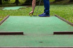 Hitting the ball on a mini golf course close up royalty free stock photo