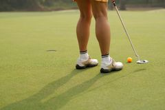 Hitting the ball with a putter Stock Image