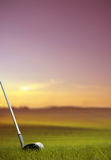 Hitting golf ball along fairway at sunset Stock Photo