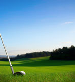 Hitting golf ball with club towards green. Hitting golf ball with club along fairway towards green Royalty Free Stock Images