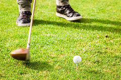 Hitting a golf ball. Detail of a driver club and a golf ball on a golf course Royalty Free Stock Image