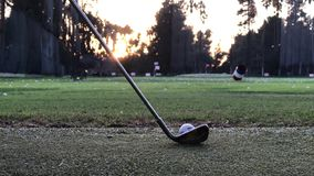Hitting a Golf Ball with an Iron. Quick, medium-power golf ball hit off the turf at a driving range in the evening stock video footage