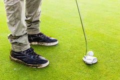 Hitting a golf ball with a putter club Stock Photos
