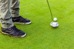 Hitting a golf ball with a putter Royalty Free Stock Image