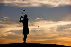 Hitting golf ball at sunset. Stock Photography