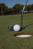 Hitting golf ball to hole Royalty Free Stock Photography