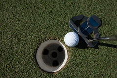 Hitting golf ball to hole Stock Images