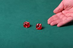 Hitting the jackpot. Dices being thrown in a craps game, or yatzee or any kind of dice involved game, Dices are a clear red color on a green felt table Royalty Free Stock Photo