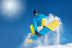 Hitting a jump. Active snowboarder in the air hitting a jump Stock Images
