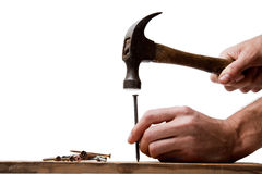 Hitting the nail on the head. A man holds a nail and hits it on the head royalty free stock photos