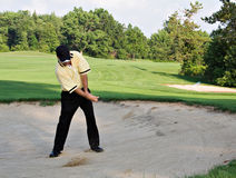 Hitting it out. Man hits ball out of sand trap - motion blur on club and ball in flight royalty free stock photography