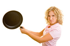 Hitting with a pan. Young woman uses a frying pan as a bat royalty free stock images