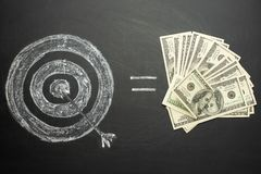 Hitting the target on a black board and equal to a lot of money, us dollars concept to achieve the goal.  royalty free stock photo
