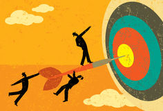 Hitting the Target. Businessmen on a dart hitting the bull's eye. The men, dart & target are on a separate labeled layer from the background Royalty Free Stock Photography
