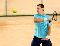 Hitting the tennis ball. Portrait of a male tennis player hitting the ball on a clay court Royalty Free Stock Image