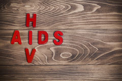 HIV AIDS red letters. On wood background stock photo