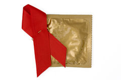 HIV Awareness and Remembrance Ribbon and Condom. Red Ribbon with gold condom wrapper on a white background Royalty Free Stock Photos