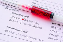 HIV infection screening test form. Sample blood in syringe on HIV infection screening test form royalty free stock photo