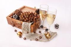 Hiver épousant des verres avec des cônes de champagne et de pin Photographie stock