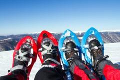 Hiver augmentant dans les montagnes sur des raquettes avec un sac à dos et une tente Photographie stock libre de droits
