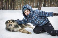 Hiver dans la forêt peu de boyb jouant avec un chien Photographie stock