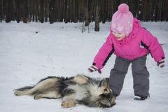 Hiver dans la petite fille de forêt jouant avec un chien Photographie stock