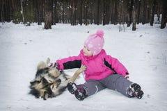 Hiver dans la petite fille de forêt jouant avec un chien Photo libre de droits