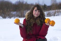 Hiver de fruits d'orange de prise de femme blanche dehors Image stock