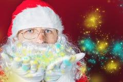 Hiver de Noël avec Santa Claus soufflant le scintillement magique Photographie stock libre de droits