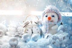 Hiver de Noël un fond, le petit bonhomme de neige se tient avec une horloge An neuf heureux Joyeux Noël Photos libres de droits