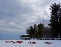 Hiver sur le lac avec des tables de pique-nique enterrées dans la neige Image stock