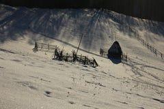 Hiver sur les collines Meule de foin et barrières Ombres le soir photos stock