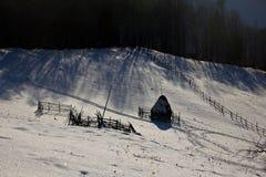 Hiver sur les collines Meule de foin et barrières Ombres le soir image stock