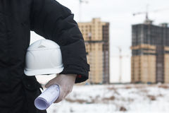 Hjälm för arkitekt- eller teknikerinnehavguling för arbetarsäkerhet på bakgrund av nya highrisehyreshusar och Royaltyfri Foto
