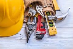 Hjälm för byggnad för läderhjälpmedelbälte på träbrädeunderhåll Co Fotografering för Bildbyråer