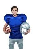 Hjälm och boll för amerikansk fotbollsspelare hållande Royaltyfri Bild