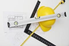 Hjälm och hjälpmedel för byggnadsritningar och byggnader Royaltyfri Foto