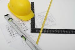 Hjälm och hjälpmedel för byggnadsritningar och byggnader Arkivbilder