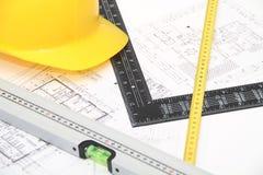 Hjälm och hjälpmedel för byggnadsritningar och byggnader Fotografering för Bildbyråer