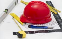 Hjälm och hjälpmedel för byggnadsritningar och byggnader arkivfoton