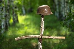 Hjälm på björkkorset Graven av en okänd tysk soldat i skogefterföljden Återställning WW2 royaltyfria foton