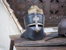 Hjälmar som är medeltida av riddare på en tabell Arkivfoton