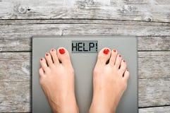 Hjälp att förlora kg med kvinnafot som kliver på en viktskala Royaltyfri Bild