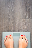 Hjälp att förlora kg med kvinnafot som kliver på en viktskala Arkivbild