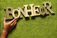 Hjälp för lycka (Bonheur) upp vid handen Grön gräsbakgrund arkivfoto